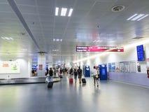 Пассажиры идя на заявку багажа аэропорта Бергама Милана в Бергаме, Италии стоковые фотографии rf