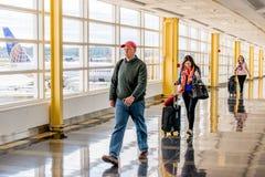 Пассажиры идя через яркий авиапорт Стоковые Изображения RF