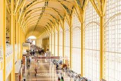 Пассажиры идя через яркий авиапорт Стоковое Изображение
