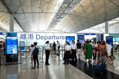Пассажиры носят багаж на международный аэропорт Гонконга стоковое фото