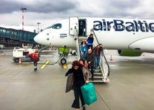 Пассажиры получают с самолета Airbaltic приехали в Ригу на дождливый день стоковое фото