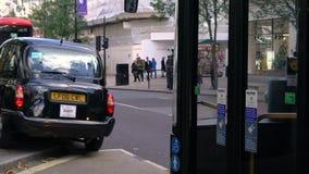 Пассажиры получая в такси и красные шины Лондона двойной палуба, улицу Оксфорда, Лондон, Англию акции видеоматериалы