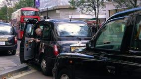 Пассажиры получая в такси и красные шины Лондона двойной палуба, улицу Оксфорда, Лондон, Англию видеоматериал