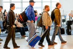 Пассажиры queued в линии для восхождения на борт на стробе отклонения Стоковая Фотография RF