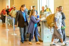 Пассажиры queued в линии для восхождения на борт на стробе отклонения Стоковые Изображения RF