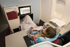 Пассажир бизнес-леди смотря кино и ослабляя во время Стоковые Фото