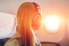 Пассажир в самолете используя наушники Женщина в плоской кабине lis Стоковое Изображение
