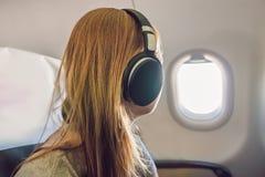 Пассажир в самолете используя наушники Женщина в плоской кабине lis Стоковые Изображения
