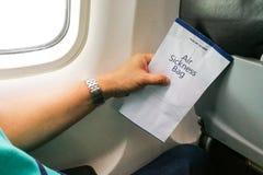 Пассажир держа сумку рвоты болезни воздуха в самолете стоковое изображение