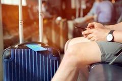 Пассажир ждет задержанный полет в аэропорте/используя мобильный телефон стоковое изображение