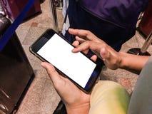 Пассажир женщины используя Smartphone в крупном аэропорте для онлайн стоковое изображение