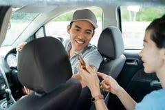 Пассажир женщины показывает смартфон для того чтобы соответствовать месту и назначению стоковая фотография