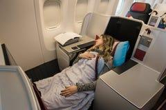 Пассажир женщины спать на предпринимательском классе самолета Стоковые Изображения RF