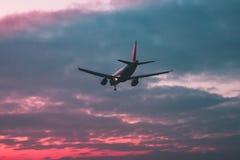 Пассажир или транспортный самолет летают на фоне красного s стоковая фотография