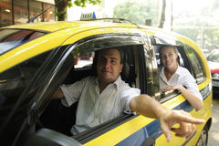 пассажир наземного ориентира водителя показывая таксомотор стоковые фото