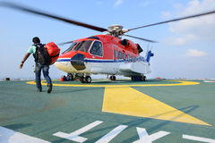 Пассажир носит его багаж для того чтобы начать вертолет на буровой вышке plat Стоковое Изображение