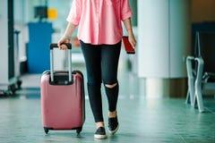 Пассажир самолета крупного плана с пасспортами и посадочным талоном и розовый багаж в салоне авиапорта Молодая женщина внутри Стоковое Изображение