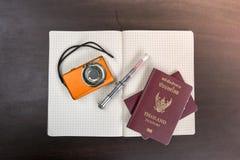 2 пасспорта Таиланда с цифровой фотокамера и книгой для того чтобы проверить lis Стоковая Фотография RF