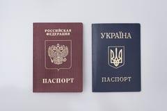 Пасспорты украинца и русских международные Белая предпосылка стоковая фотография rf