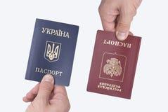Пасспорты украинца и русских международные в руке ` s человека стоковое изображение