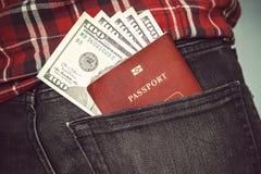 Пасспорт в задних джинсах pocket с американскими долларами Стоковые Фотографии RF