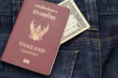 Пасспорт и доллар Таиланда получают надевать наличными голубые брюки демикотона, это Стоковая Фотография RF