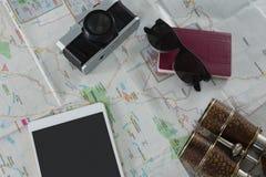 Пасспорт, камера, бинокли и цифровая таблетка на карте Стоковые Фотографии RF