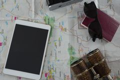 Пасспорт, камера, бинокли и цифровая таблетка на карте Стоковые Фото