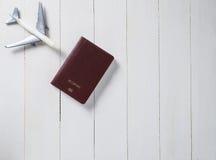 Пасспорт путешественника самолета на белой деревянной предпосылке Стоковая Фотография
