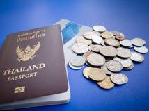 Пасспорт Таиланда с международной книгой банка монетки и сбережений на голубой предпосылке Стоковое Изображение RF