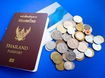 Пасспорт Таиланда с международной книгой банка монетки и сбережений на голубой предпосылке Стоковые Изображения RF