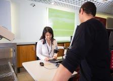 Пасспорт штата рассматривая пассажира на регистрации авиапорта Стоковое фото RF