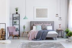 Пастельная спальня с удобным стулом стоковые изображения rf