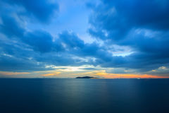 Пастельный заход солнца над океаном в облачном небе Стоковое фото RF