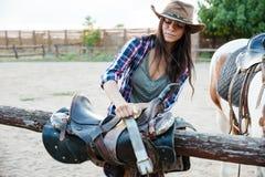Пастушка женщины в шляпе подготавливая седловину для верховой лошади Стоковые Фотографии RF