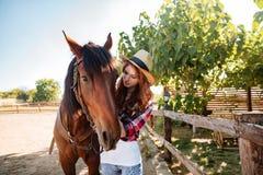 Пастушка женщины Redhead позаботить о ее лошадь на ферме Стоковое Изображение RF