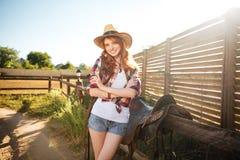 Пастушка радостного redhead молодая подготавливая седловину для верховой лошади Стоковое Изображение RF