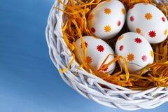 4 пасхального яйца в корзине на голубой предпосылке Стоковые Изображения