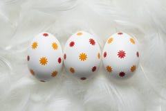3 пасхального яйца на белых пер Стоковая Фотография