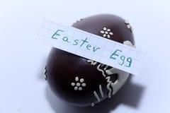 Пасхальное яйцо написанное на белом примечании, пасхальное яйцо на предпосылке Стоковая Фотография