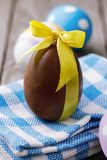 Пасхальное яйцо сделанное из шоколада, связанный с желтой лентой Стоковые Фотографии RF