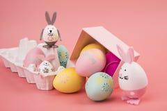 Пасхальное яйцо с розовой темой в подарочной коробке яйцо украшено как милый зайчик играя с другим зайчиком, на розовом backgroun стоковое фото