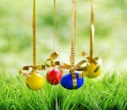 Пасхальные яйца вися на золотистых тесемках Стоковые Изображения RF