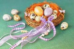 Пасхальные яйца в гнезде с декоративными лентами на зеленой предпосылке Стоковое Изображение RF