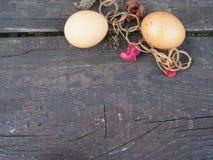 Пасхальные яйца в корзине с украшениями на таблице стоковые фотографии rf