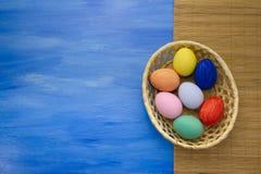 Пасхальные яйца в корзине yello на голубой предпосылке S1V1 Стоковые Фото