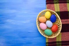 Пасхальные яйца в корзине yello на предпосылках S1V20 сини и ткани Стоковая Фотография RF