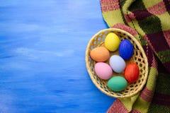 Пасхальные яйца в корзине yello на предпосылках S1V15 сини и ткани Стоковое Изображение RF