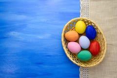 Пасхальные яйца в корзине yello на предпосылках S1V14 сини и ткани Стоковое фото RF