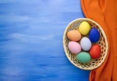 Пасхальные яйца в корзине yello на предпосылках S1V13 сини и ткани Стоковое Изображение RF